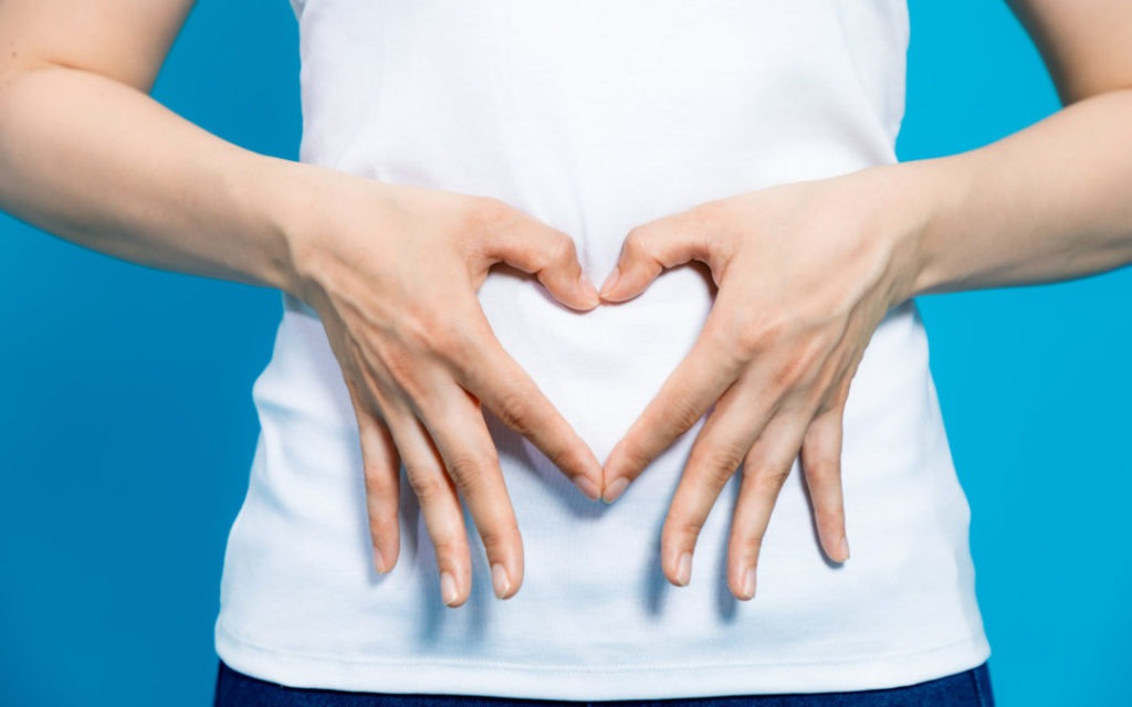 hands making heart shape on stomach